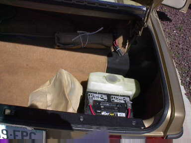 The battery and washer tank are mounted in the trunk